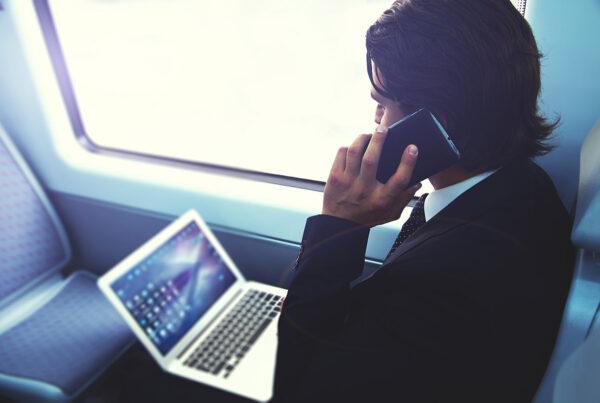 Uomo che parla al cellulare con computer portatile